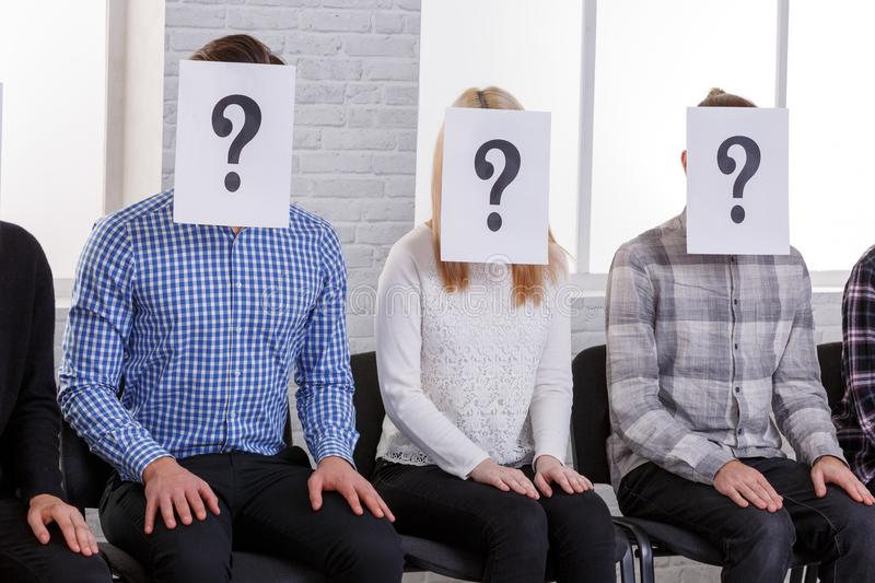 A group of people are sitting on chairs with faces covered with leaflets with a question mark close-up. A group of people are sitting on chairs with closed faces stock photos