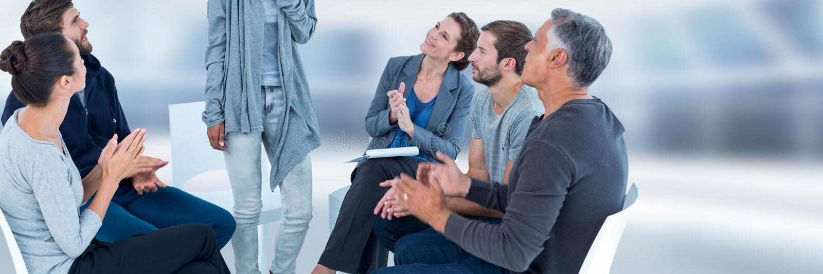 Group of People sitting in circle with ladt standing up and clapping hands stock photo