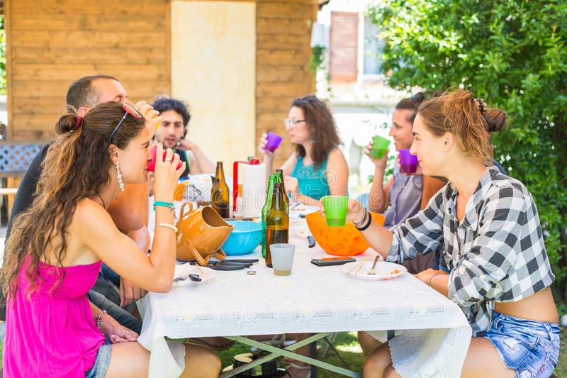 Group of people sitting having lunch together and drinking stock photography
