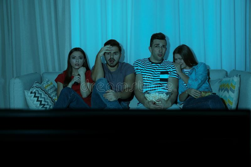 Group of people with snacks watching TV together on couch. In dark room royalty free stock photos