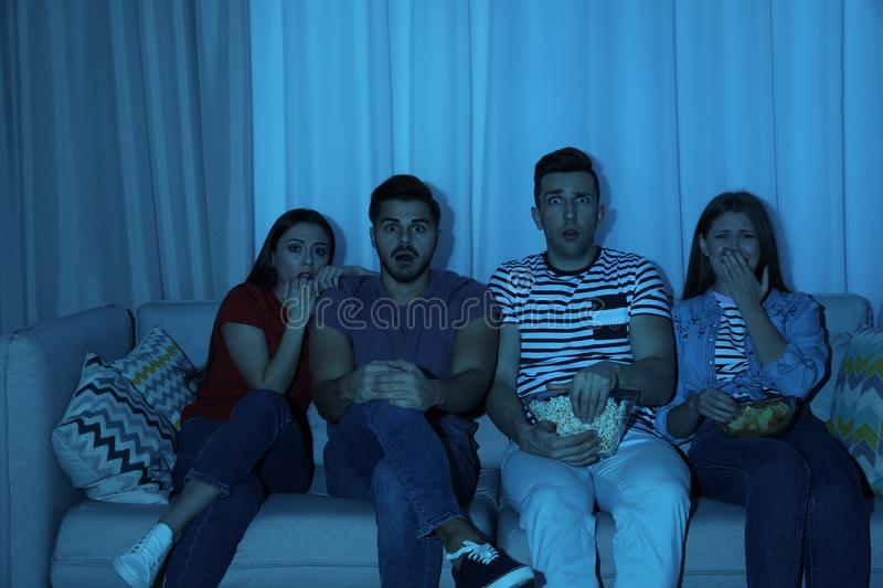 Group of people with snacks watching TV together on couch. In dark room stock photos