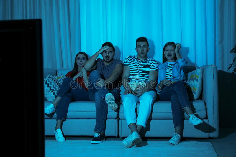 Group of people with snacks watching TV together on couch. In dark room stock photo