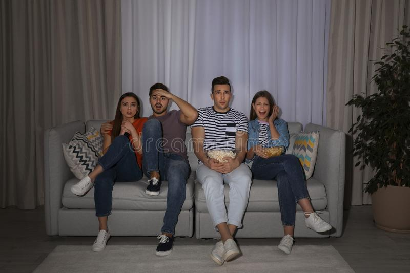 Group of people with snacks watching TV together on couch. In dark room royalty free stock photo