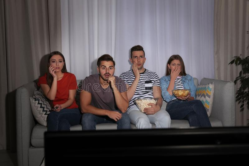 Group of people with snacks watching TV together. On couch in dark room royalty free stock photo