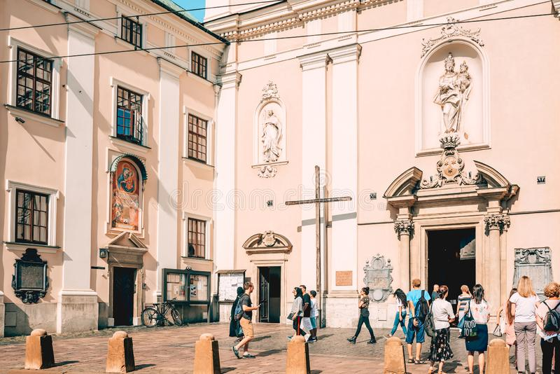 Group of people standing in front of church in old town Krakow, Poland. People are standing and passing by Our Lady in Piasek Church on Karmelicka Street in royalty free stock photos