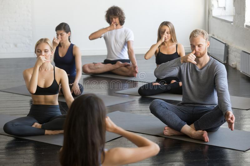 Group of people in Sukhasana pose making nadi shodhana pranayama. Group of young sporty people practicing yoga lesson with instructor, making nadi shodhana royalty free stock photography
