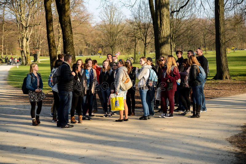 Group of people taking a guided tour. A group of people take a guided walking tour of the Englischer Garten in Munich,Germany royalty free stock photo