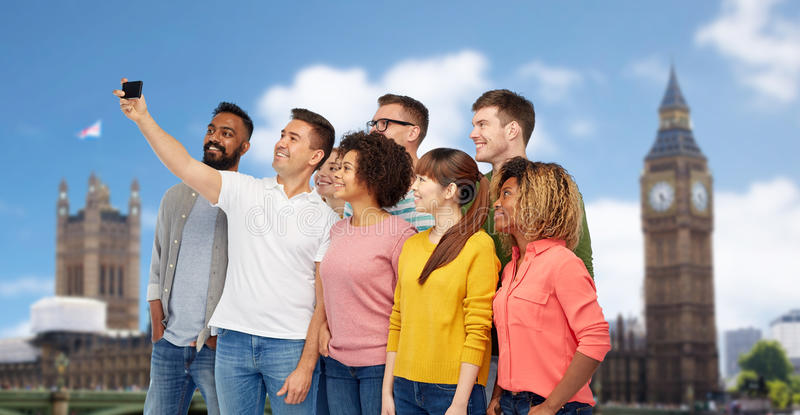 Group of people taking selfie by smartphone. Travel, tourism, diversity, technology and people concept - international group of happy smiling men and women stock photos
