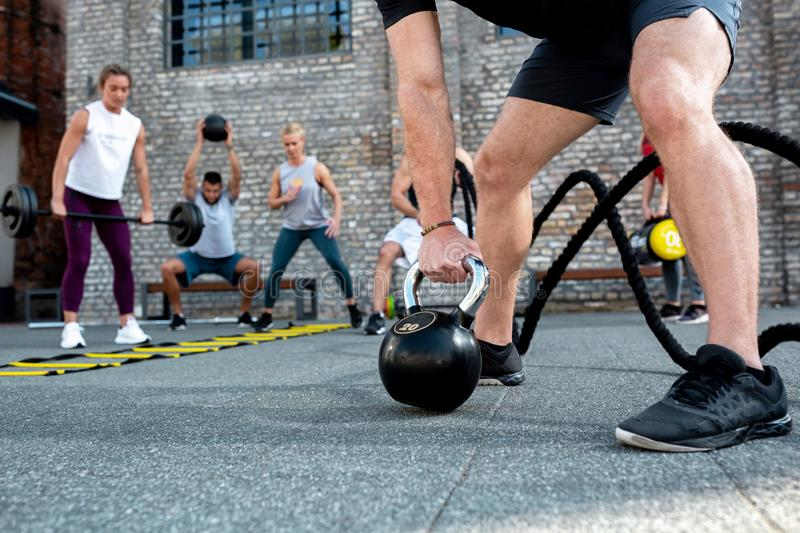 Group of people training, black kettlebell stock image