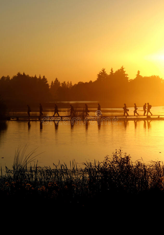 A group of people walking on the footpath on water stock photography