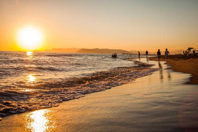 Group of People Walking at the Shoreline during Golden Hour stock photos