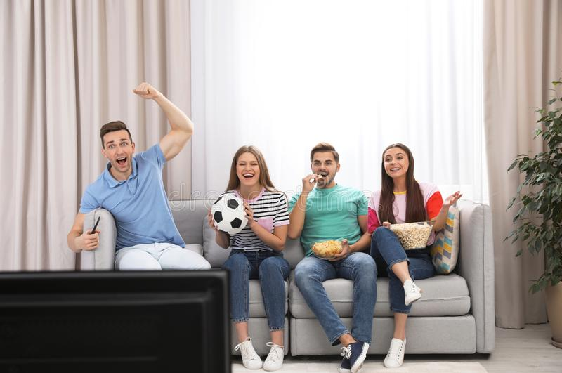 Group of people watching soccer match on TV stock photography