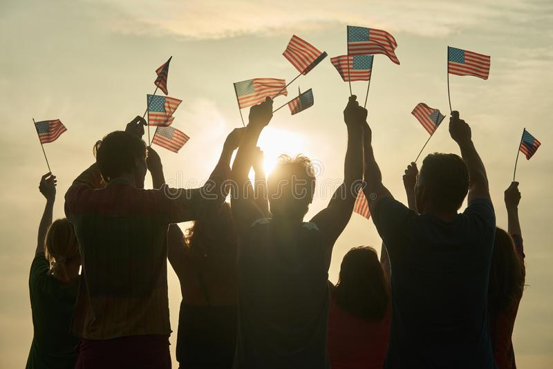 Group of people waving American flags. Silhouette of people with usa flags against evening sunny sky background stock photography