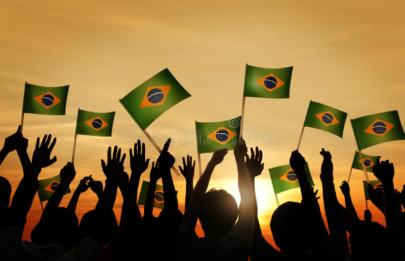 Group of People Waving Brazilian Flags in Back Lit stock images