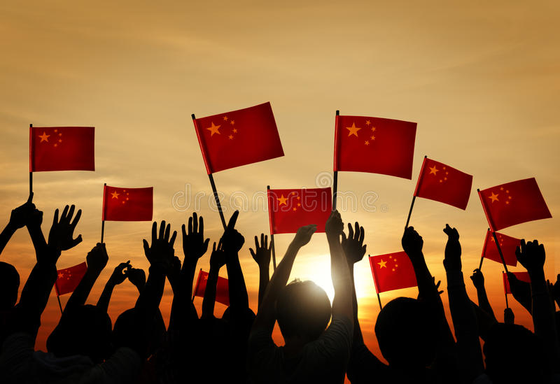 Group of People Waving Chinese Flags in Back Lit.  royalty free stock image