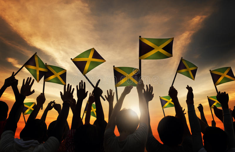 Group of People Waving Flag of Jamaica in Back Lit.  stock photos