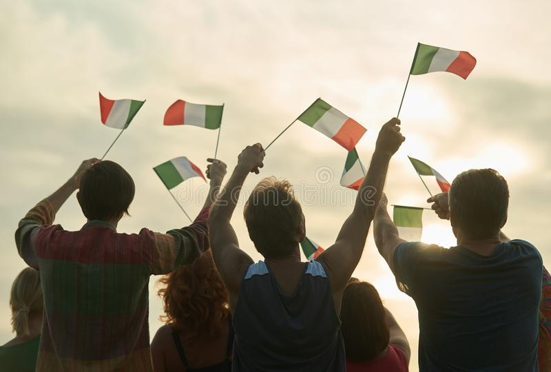 Group of people waving italian flags. Italy family against evening sky background stock photo
