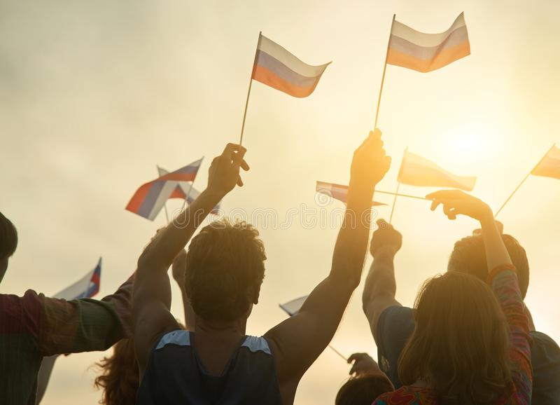 Group of people waving russian flags. Evening sunny sky background stock photo