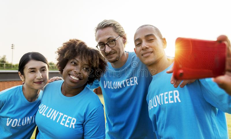 Group of People Wearing Blue Volunteer Shirts stock images