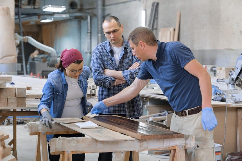 Group of people working in carpentry workshop. Process of varnishing wooden board with oil. Furniture joinery wood business royalty free stock photos