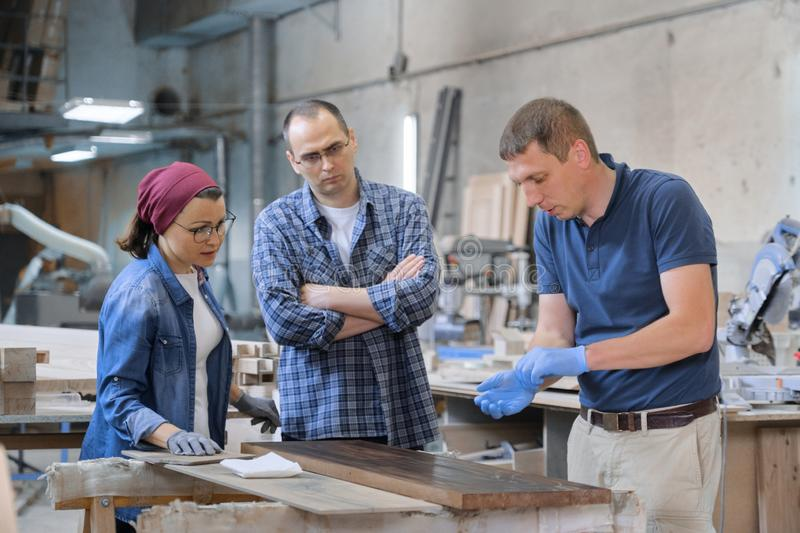 Group of people working in carpentry workshop. Process of varnishing wooden board with oil. Furniture joinery wood business royalty free stock image