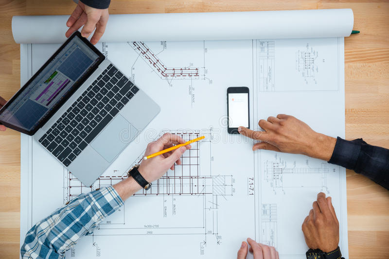 Group of people working with laptop smartphone and blueprint stock download group of people working with laptop smartphone and blueprint stock image image of malvernweather Choice Image