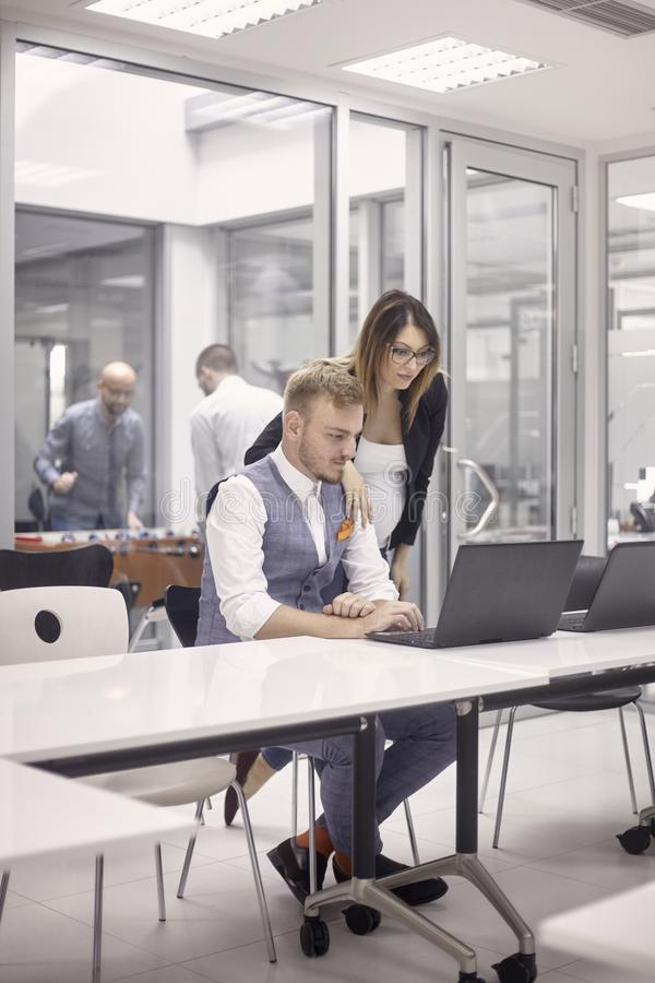 Group of people, working together on laptop, some relaxing playing table football, indoors modern office building royalty free stock photo