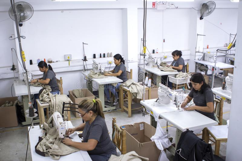 Group of Peruvian workers with sewing machine making alterations to clothes. stock photos