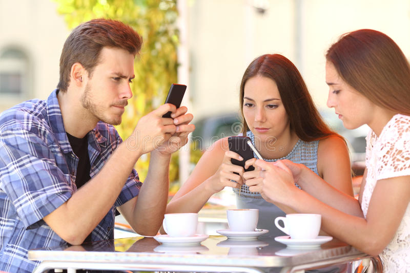 Group of phone addicted friends in a coffee shop. Group of three smart phone addicted friends in a coffee shop terrace everyone with one cellphone