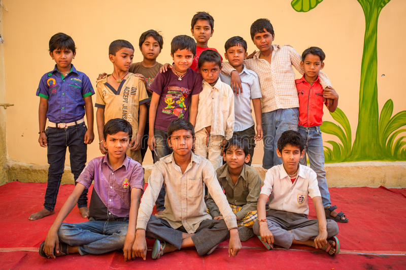 Group photo of Indian boys. GODWAR REGION, INDIA - 15 FEBRUARY 2015: Boys pose for a group photo in front of wall on red carpet during preparation of wedding stock images