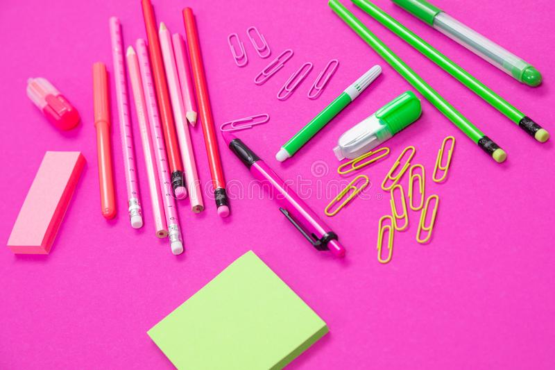 Group of pink and bright green office incidentals on pink background isolated royalty free stock photography