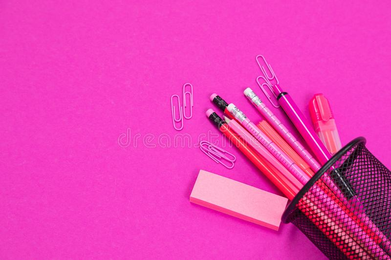 Group of pink color stationery products is spilled from pencil box on pink surface flatlay isolated royalty free stock images