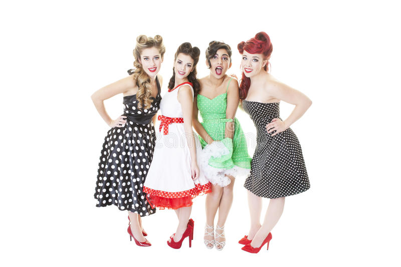 Group of Pinup girls. A group of four young girls dressed in Rockabilly, pinup dresses. Shot on white background stock image
