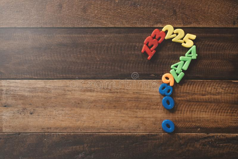 Group of plastic toy numbers forming question mark on a wooden table. Concept of Questions, faq and mathematical problems royalty free stock photography