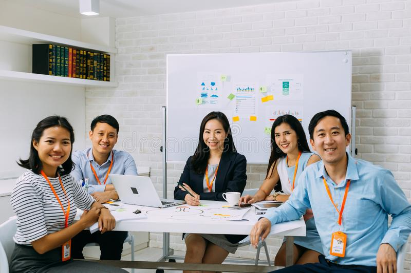 Group portrait of Asian business people smiling and looking at camera at meeting stock photos