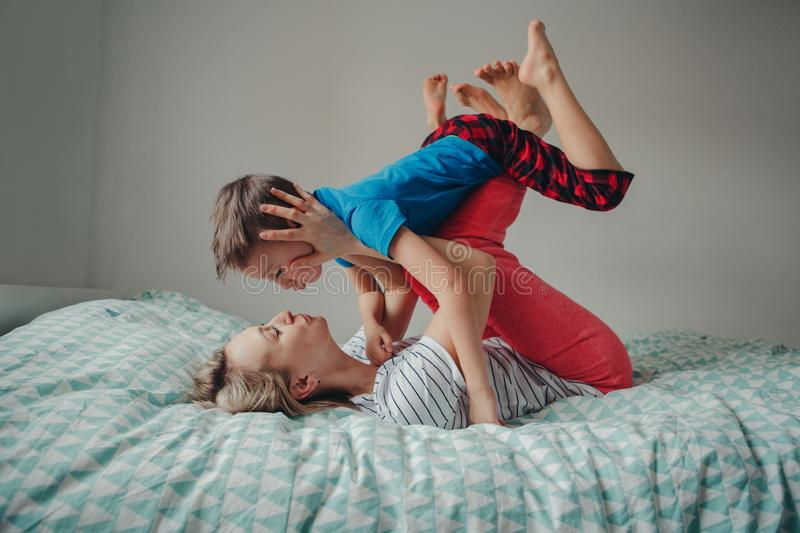 Caucasian mother and boy son playing together in bedroom at home stock photography