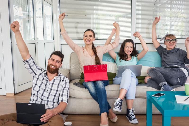 Successful remote workers looking at camera sharing a modern co-. Group portrait of four happy and successful remote workers looking at camera with raised arms stock photos