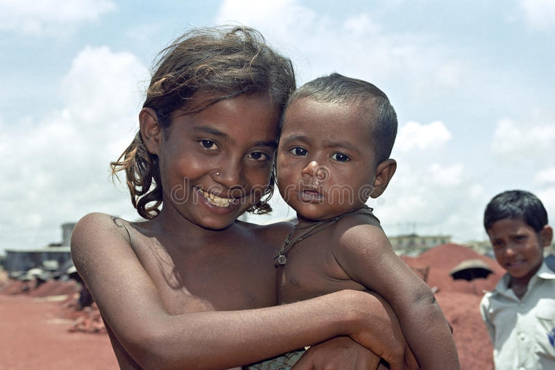 Group portrait of poor Bangladeshi children. BANGLADESH capital city DHAKA: Group portrait of a smiling, cheerful girl with her brother in the arm during her stock photos