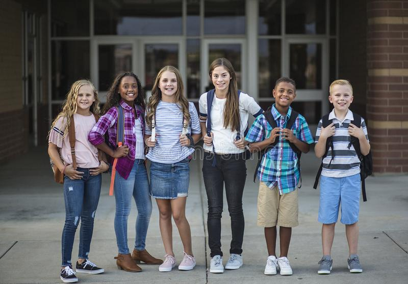 Group portrait of pre-adolescent school kids smiling in front of the school building. Large Group portrait of pre-adolescent school kids smiling in front of the royalty free stock photo