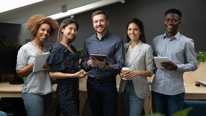 Group portrait of smiling multiethnic team posing in office stock photography