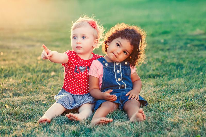 White Caucasian and latin hispanic babies hugging outside in park. royalty free stock photo