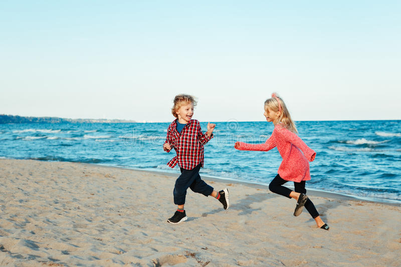Group portrait of two funny white Caucasian children kids friends playing running on beach on sunset stock photography