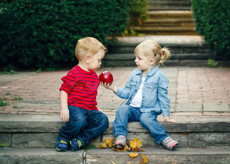 Group portrait of two white Caucasian cute adorable funny children toddlers sitting together sharing apple food royalty free stock photo