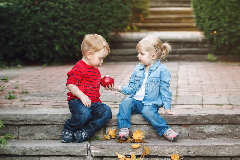 Two white Caucasian cute adorable funny children toddlers sitting together sharing eating apple food royalty free stock photos
