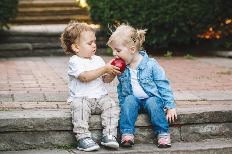 Two white Caucasian cute adorable funny children toddlers sitting together sharing eating apple food stock image