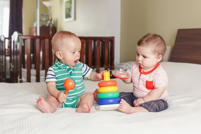 Funny baby boys sitting together on bed playing stacking rings toy. Group portrait of two white Caucasian cute funny baby boys sitting together on bed playing royalty free stock images