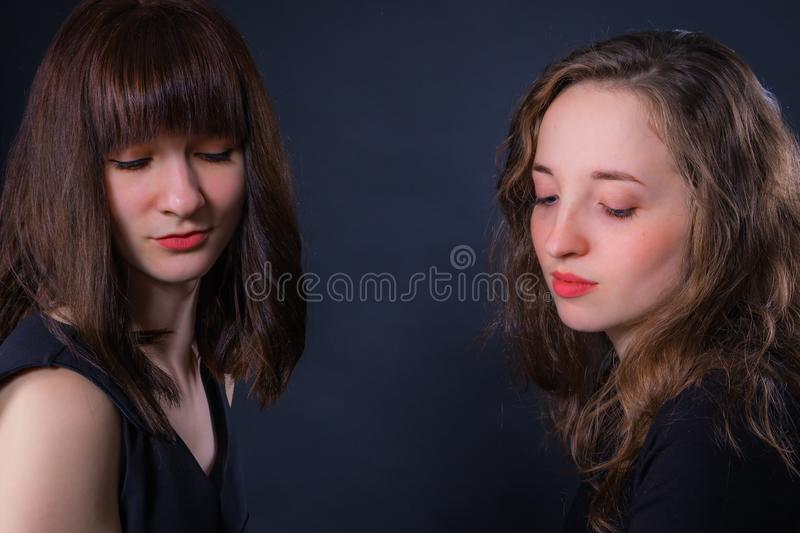 Group portrait of two girls on a dark background royalty free stock photography