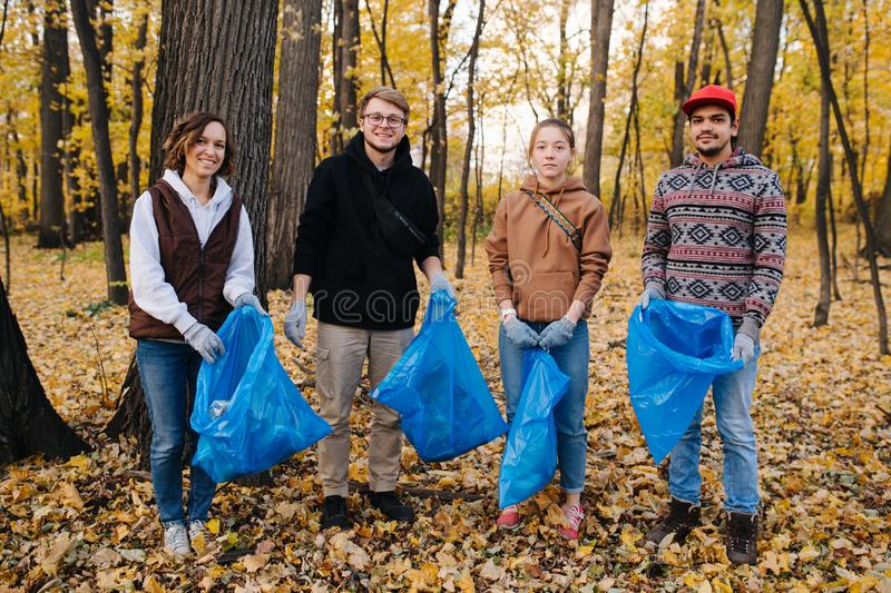 Group portrait of volunteers with trash bags in a seasonal forest at autumn royalty free stock image