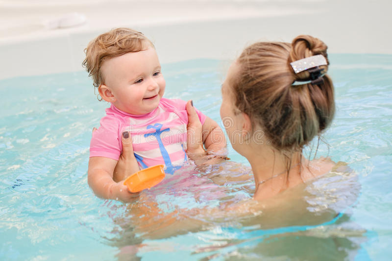 Group portrait of white Caucasian mother and baby daughter playing in water in swimming pool. Group portrait of white Caucasian mother and baby daughter playing stock image