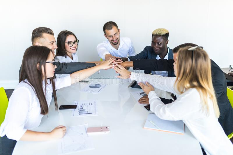 Group of positive happy smile young business people pile of hands at desk office. Businesspeople putting their hands on top of stock photos